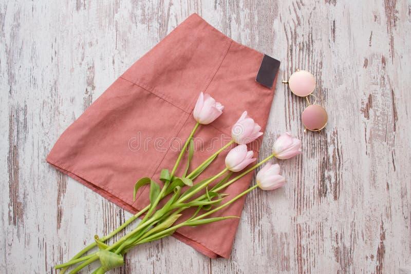 модная концепция Розовая юбка, стекла и розовые тюльпаны Взгляд сверху, предпосылка света деревянная стоковые изображения