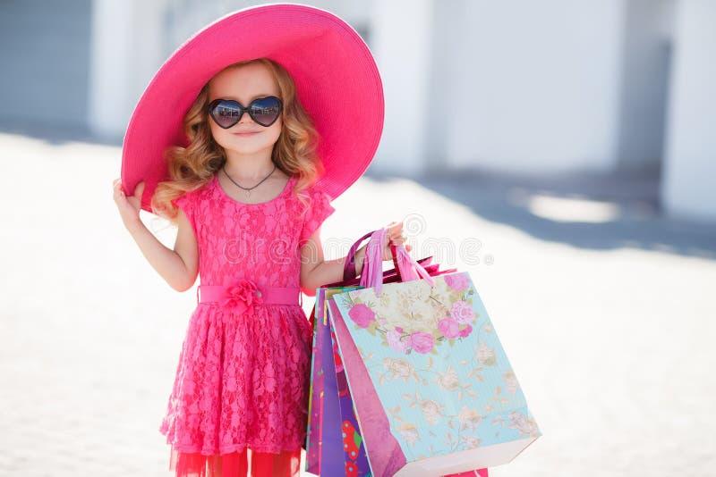 Модная маленькая девочка в шляпе с хозяйственными сумками стоковые фотографии rf