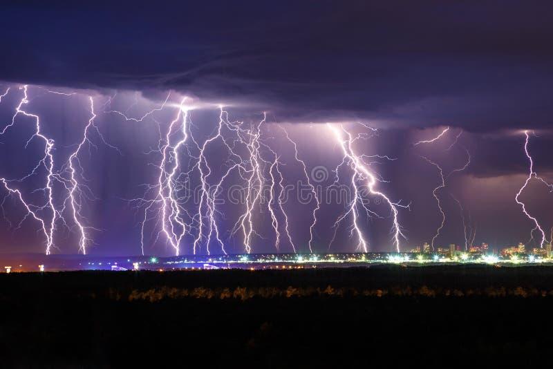 Молния грома ночи над небом города стоковые фото