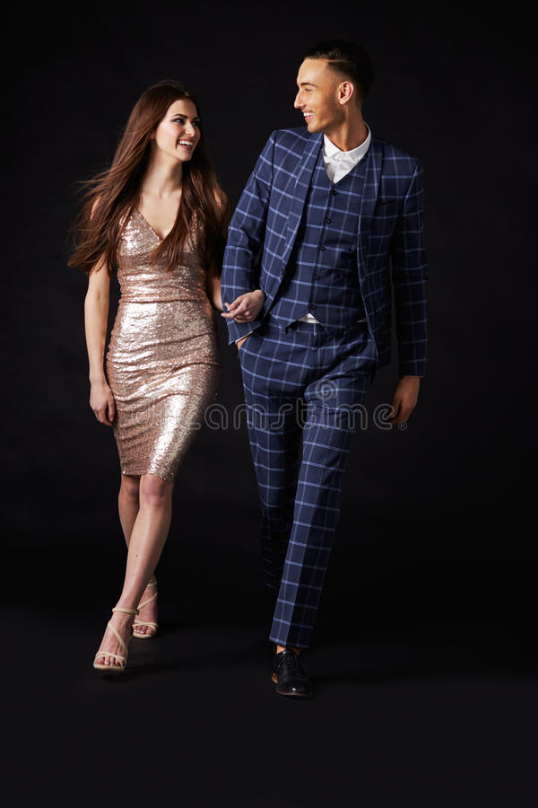 Модные молодые пары идя совместно рука в руке стоковое изображение