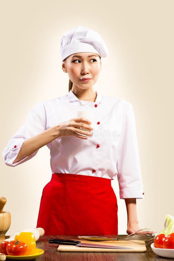 Молоко азиатского женского кашевара выпивая стоковое фото rf