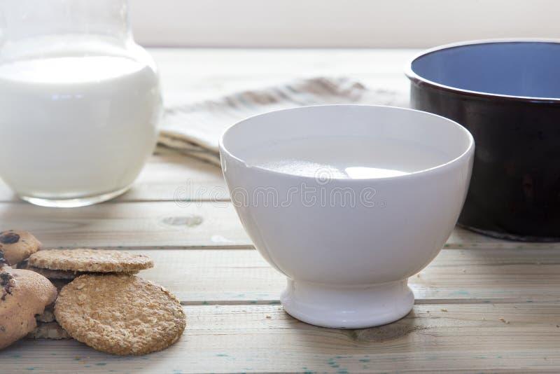Молоко кастрюльки лить в шаре, который нужно позавтракать стоковая фотография rf