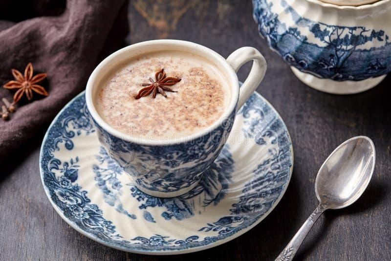 Молоко с spiced ingridients, ручка latte chai чая Masala традиционное теплое индийское сладостное циннамона, имбирь, травы, специ стоковые изображения