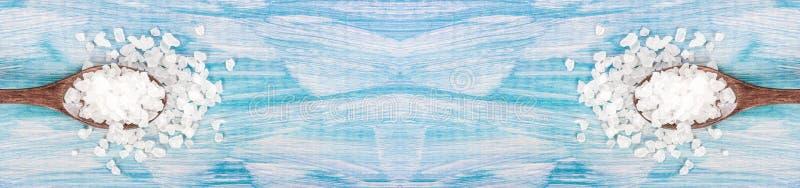 Молотилка соли моря на деревянном свете - ложке голубой затрапезной таблицы деревянной Кухня и косметическое здоровое использован стоковое изображение