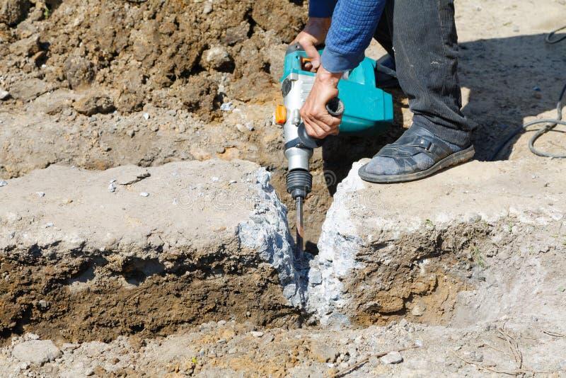 Молоток работника ломает бетон стоковое изображение