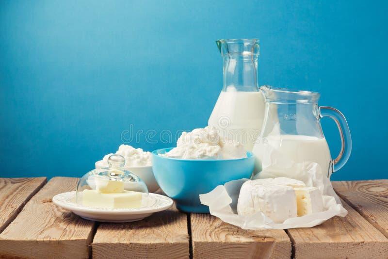 Молочные продучты на деревянном столе над голубой предпосылкой стоковые фотографии rf
