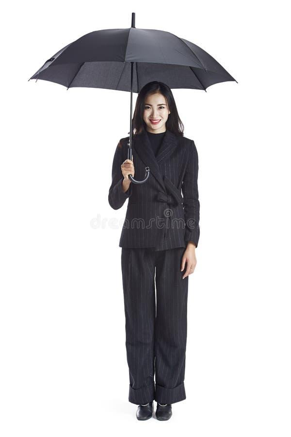 Молодая азиатская бизнес-леди держа зонтик стоковые фото