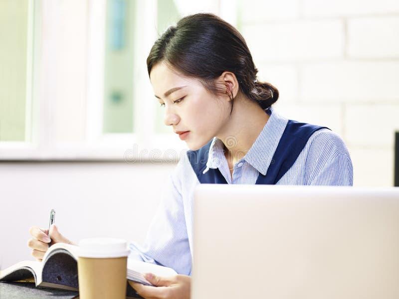 Молодая азиатская бизнес-леди работая в офисе стоковая фотография