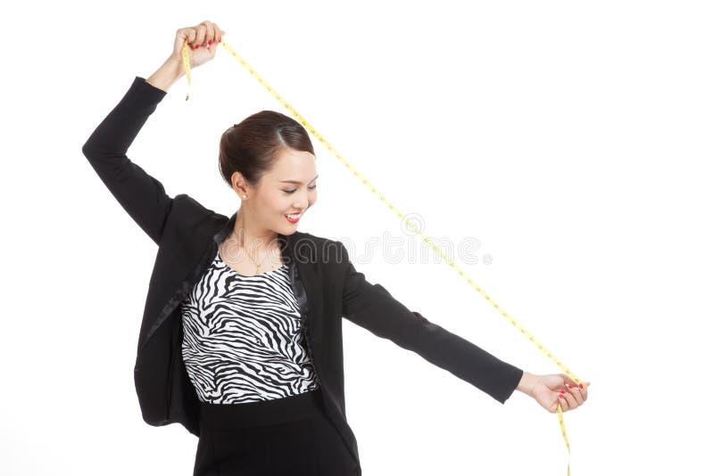 Молодая азиатская бизнес-леди с измеряя лентой стоковое фото rf