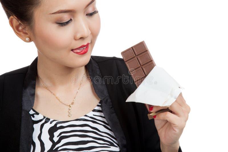 Молодая азиатская бизнес-леди хочет съесть шоколад стоковые фото