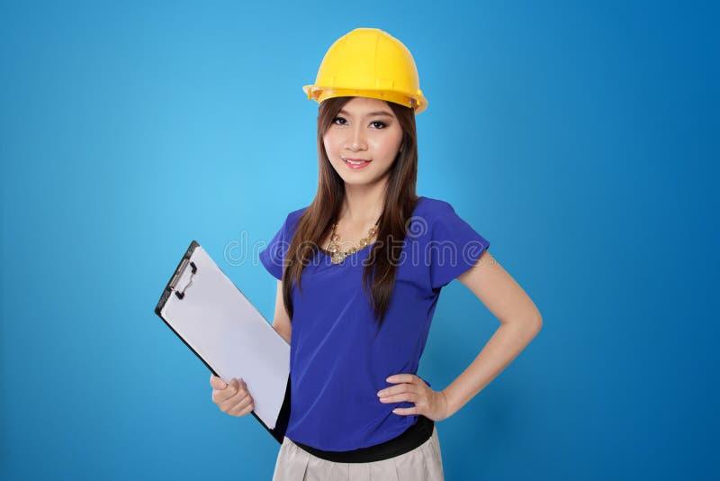 Молодая азиатская женщина архитектора в желтой трудной шляпе, на живой голубой предпосылке стоковые изображения