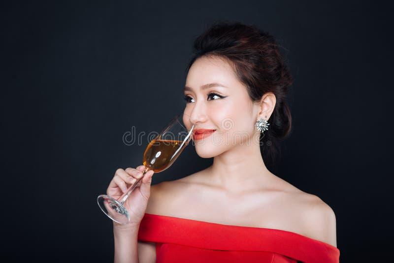 Молодая азиатская женщина в роскошном красном платье с стеклом сверкная wi стоковая фотография
