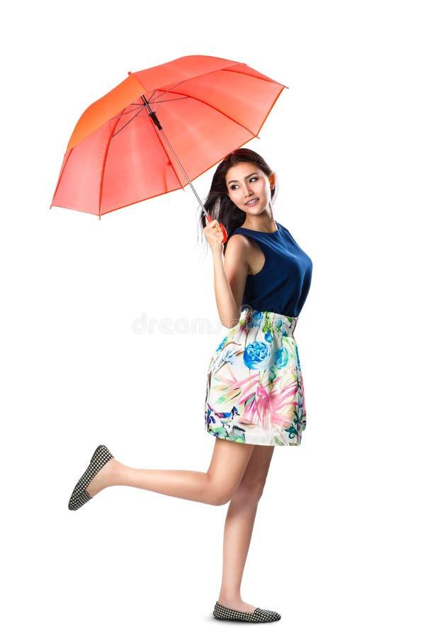 Молодая азиатская женщина держа зонтик в ветре стоковые изображения