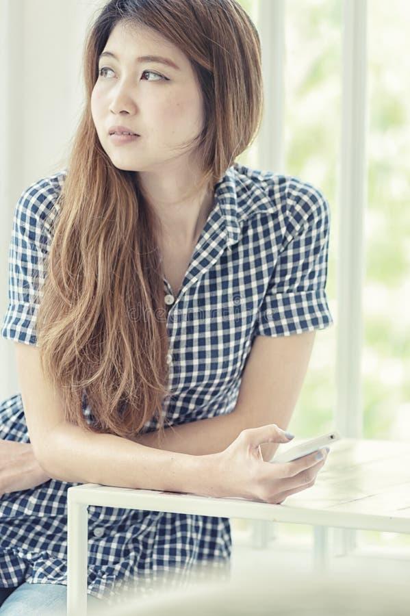 Молодая азиатская женщина используя умный телефон в кафе стоковые фотографии rf