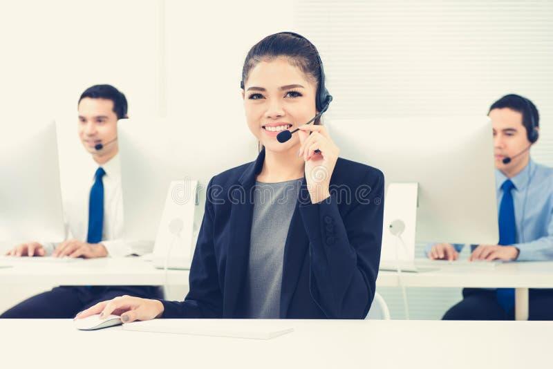 Молодая азиатская женщина как оператор работая в центре телефонного обслуживания стоковые изображения