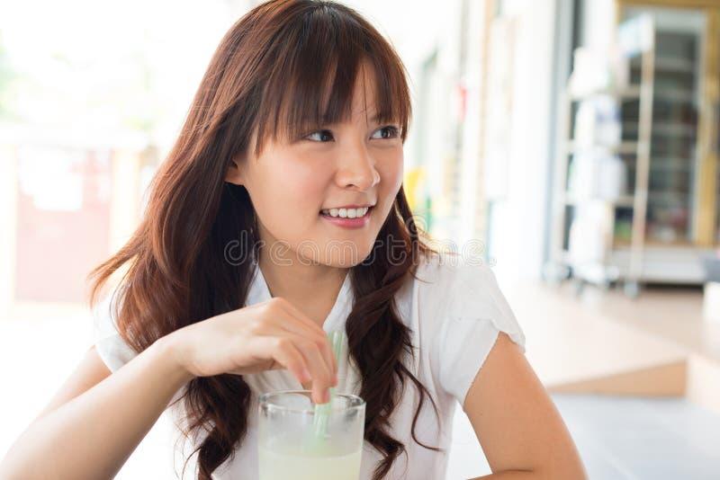 Молодая азиатская женщина наслаждаясь пить стоковые изображения