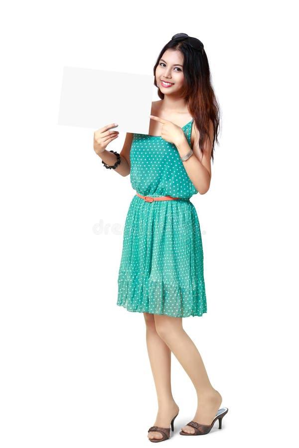 Молодая азиатская женщина показывая чистый лист бумаги стоковые фото