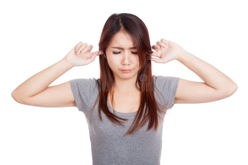 Молодая азиатская женщина покрывая ее уши стоковые фото