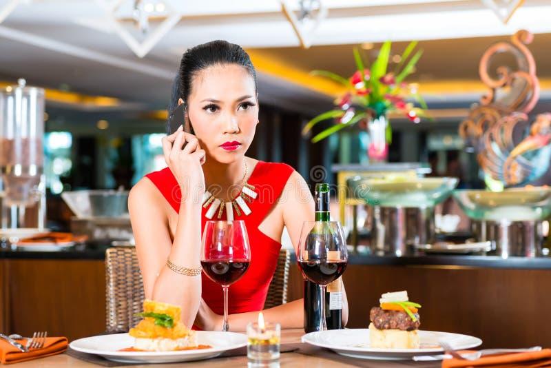Download Молодая азиатская женщина сидя в ресторане Стоковое Фото - изображение насчитывающей женщина, обед: 41662988