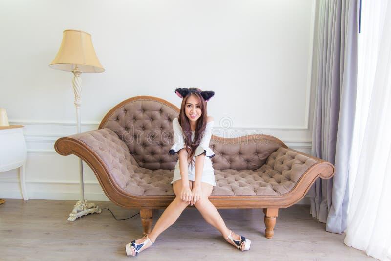 Download Молодая азиатская женщина улыбки сидя на кресле в современной комнате Стоковое Фото - изображение насчитывающей наслаждение, кожа: 41655548