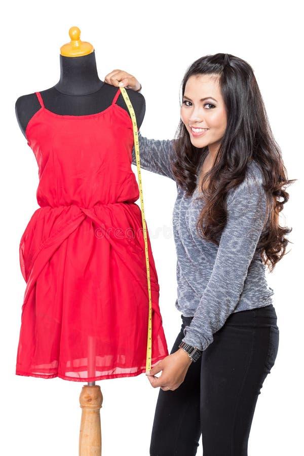 Молодая азиатская дизайнерская женщина измеряя и усмехаясь, взгляд на c стоковое изображение