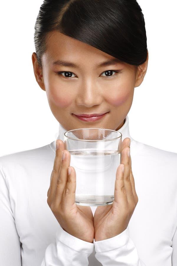 Молодая азиатская китайская женщина наслаждаясь стеклом воды стоковые фотографии rf