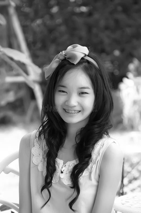Молодая азиатская китайская женщина усмехаясь в белом платье с железным brac стоковая фотография