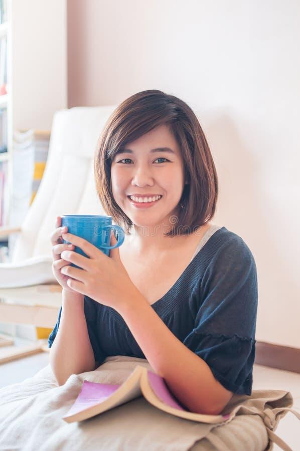 Молодая азиатская книга чтения женщины и выпивая кофе стоковое изображение rf
