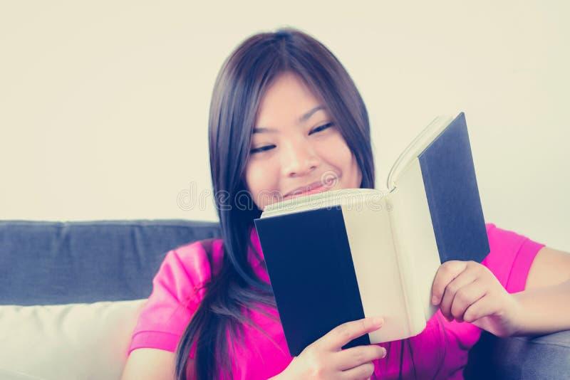 Молодая азиатская книга чтения женщины с усмехаясь стороной стоковые изображения