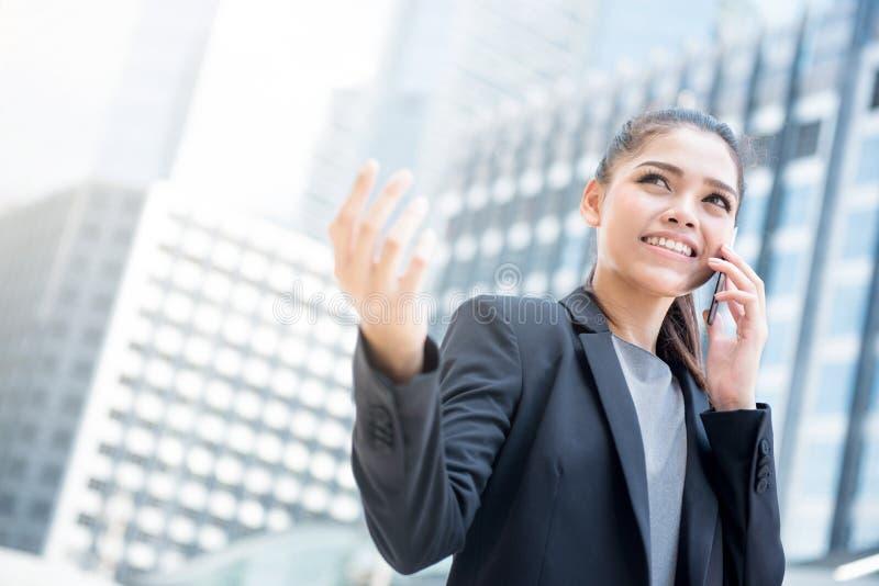 Молодая азиатская коммерсантка говоря на мобильном телефоне стоковая фотография rf