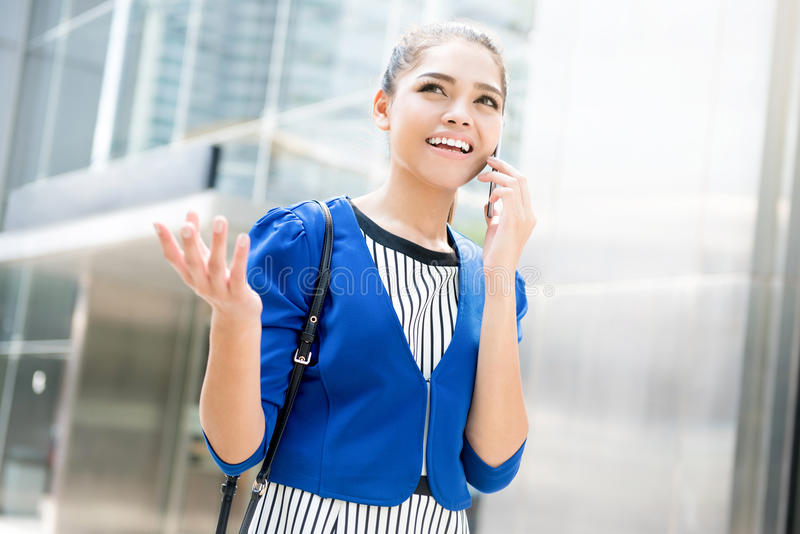 Молодая азиатская коммерсантка говоря на smartphone с жестом рукой стоковое изображение rf
