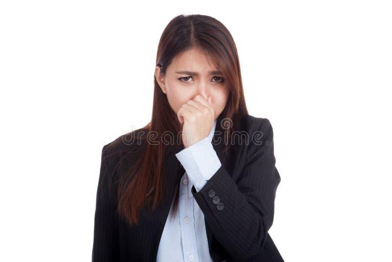 Молодая азиатская коммерсантка держа ее нос из-за плохого smel стоковая фотография rf