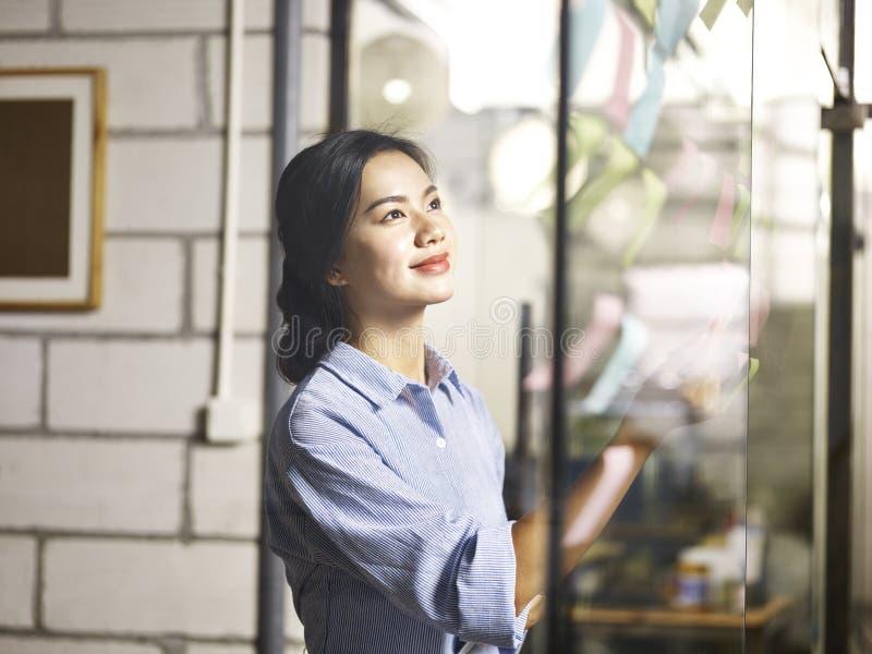 Молодая азиатская коммерсантка делая бизнес-план стоковые изображения