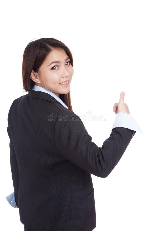 Молодая азиатская коммерсантка поворачивает назад большие пальцы руки вверх стоковое фото rf
