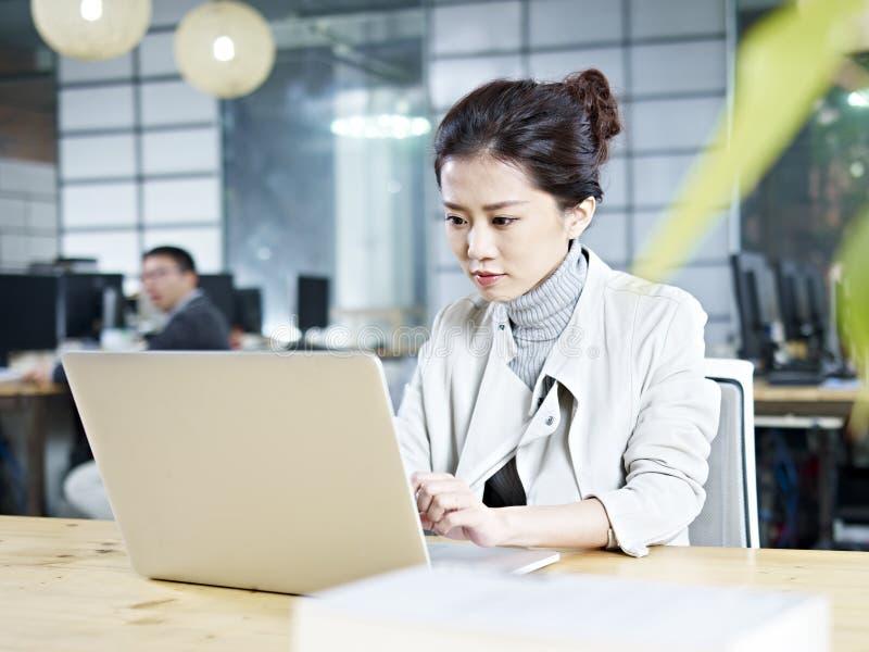 Молодая азиатская коммерсантка работая в офисе стоковое изображение