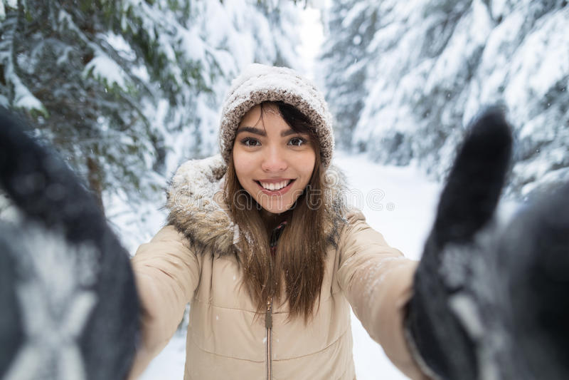 Молодая азиатская красивая камера улыбки женщины принимая фото Selfie в девушке леса снега зимы Outdoors стоковое изображение rf
