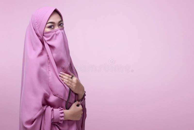 Молодая азиатская мусульманская женщина в вуали с стоять шариков молитве стоковое фото rf