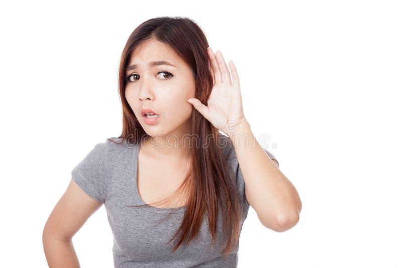 Молодая азиатская попытка женщины, который нужно слушать с рукой к уху стоковое фото