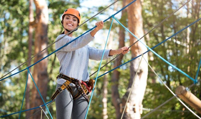 Молодая активная женщина делая максимум ropes курс стоковое фото rf
