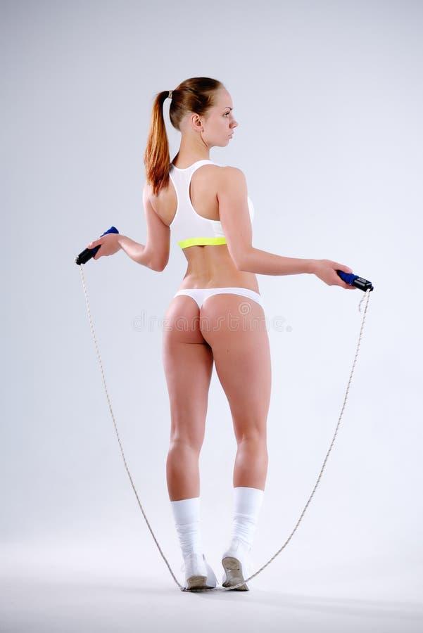 Молодая активная женщина с веревочкой скачки в студии стоковые изображения rf