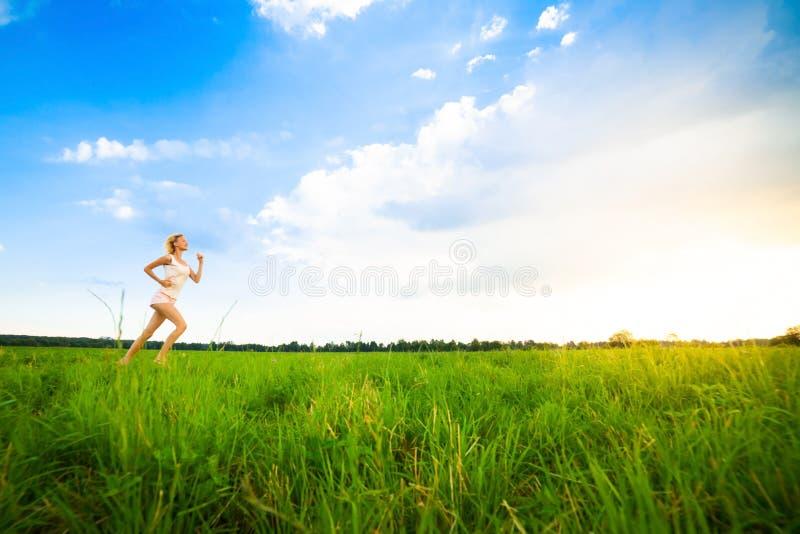 Молодая дама бежать на сельской дороге во время захода солнца стоковое изображение rf