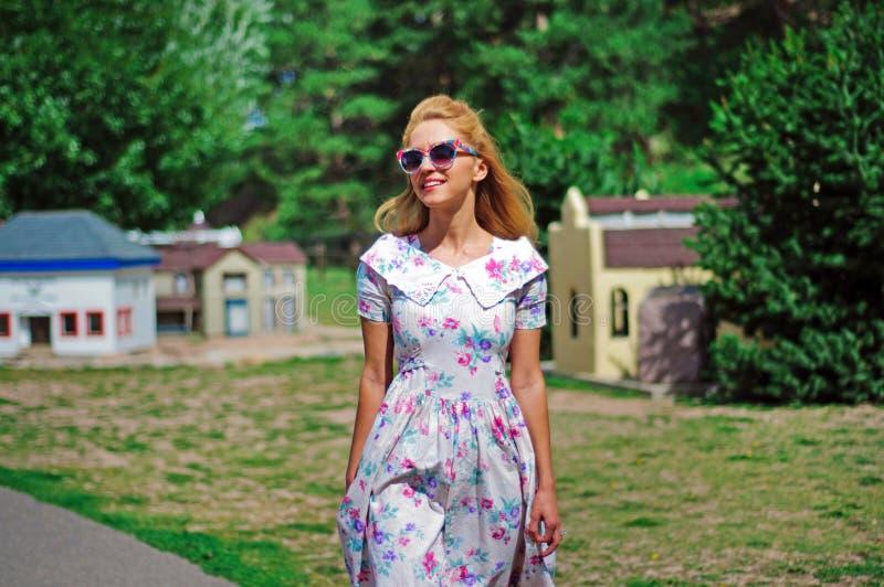 Молодая дама в винтажном платье и солнечных очках стоковые фотографии rf