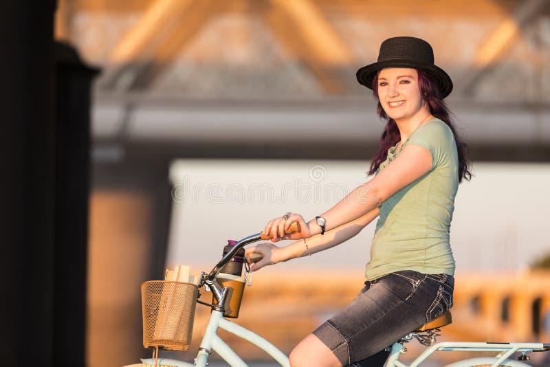 Молодая дама ехать велосипед на заходе солнца стоковые фотографии rf