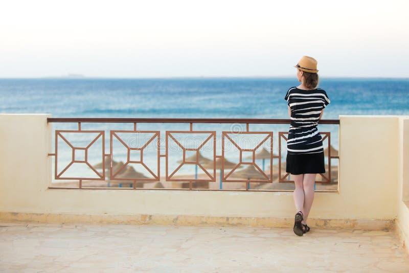 Молодая дама на балконе с видом на море стоковое фото rf