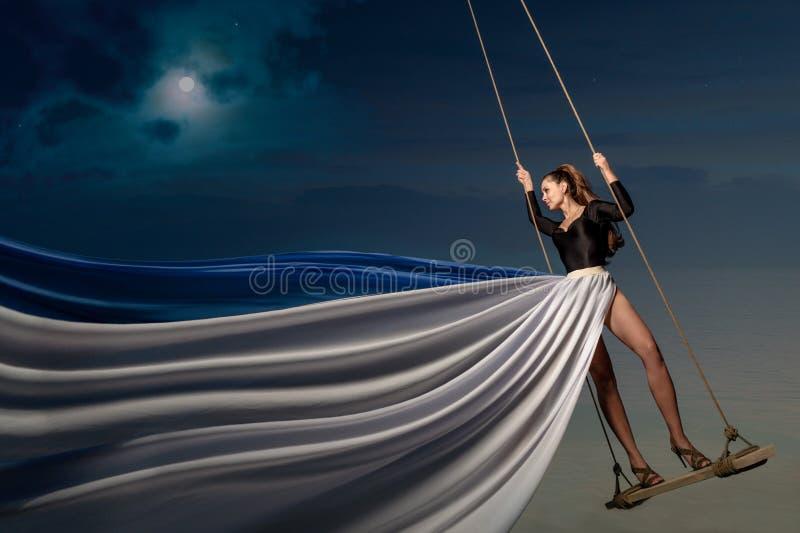 Молодая дама на качании над водой стоковые фотографии rf