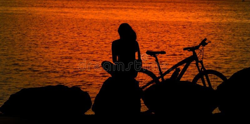Молодая дама сидя на утесе с велосипедом стоковые фотографии rf