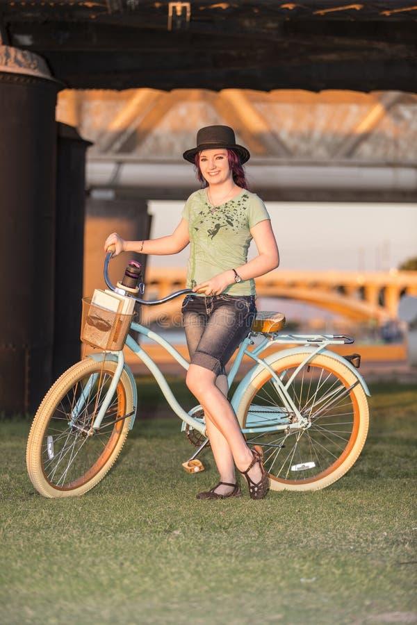 Молодая дама стоя с велосипедом на заходе солнца стоковое фото rf