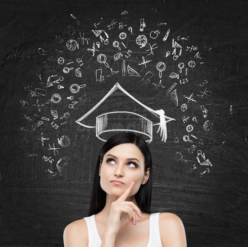 Молодая дама думает о изучать в университете Воспитательные значки нарисованы на черной доске мела стоковые фотографии rf