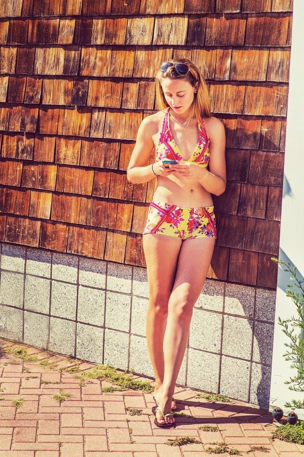 Молодая американская женщина отправляя СМС на пляже, ослабляя стоковое изображение rf