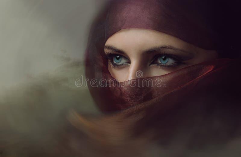 Молодая аравийская женщина в hijab с сексуальными голубыми глазами стоковая фотография rf